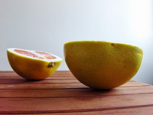 Photo of pomelo halves resting on a wooden table.