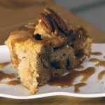 A square slice of apple cake topped with a toasted pecan and drizzled with a glaze.