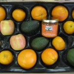 CSA Box with tangerines, oranges, apples, avocados, and a jar of apricot conserve