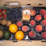 CSA Box with peaches, oranges, avocados, kiwis, strawberries, blueberries, and granola