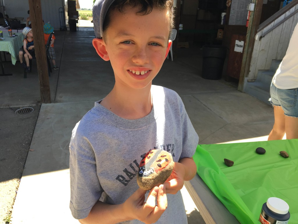 child with lady bug rock craft