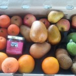 CSA box filled with pears, apples, feijoa, oranges, apples, and a jar of conserve.