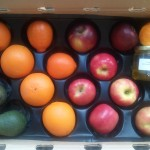 CSA Box filled with apples, oranges, tangelos, avocados, and a jar of olive oil.